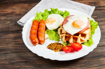 Belgian waffle with egg and sausage on wood table