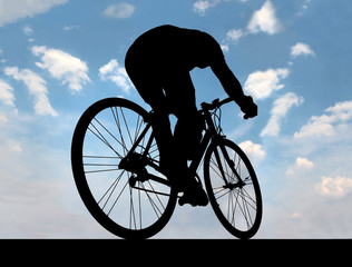 silhouette of cyclist against the blue sky when he goes on road
