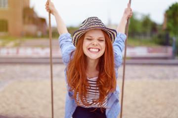 lachende frau mit sommerhut steht auf einer schaukel in der stadt