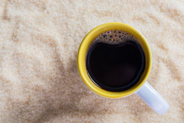Coffee latte with a cup on sugar background.
