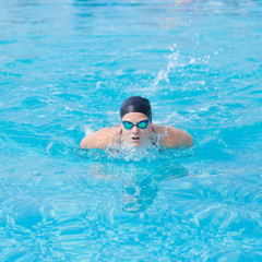 Young girl in goggles and cap swimming butterfly stroke style in the blue water pool