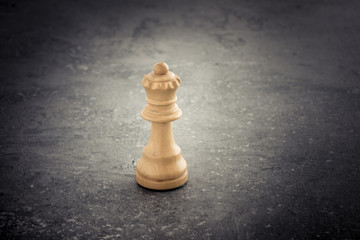 One white chess queen standing alone on stone table with copy space. Concept of strategy, competition and  leadership.
