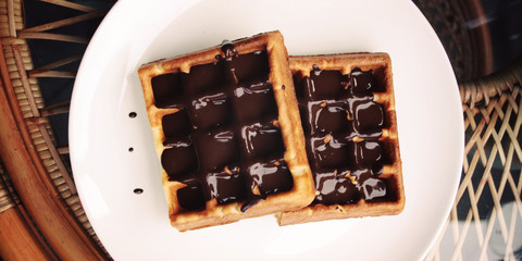 Vienna Waffles with chocolate topping. Aged. Delicious dessert. White plate with Chocolate covered Wafers. Toned. Delicious dessert. Wide photo for wallpaper or site slider. Unhealthy but delicious.