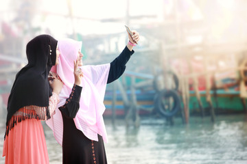 Two happy young muslim girls with Hijab making selfie photo on smartphone.Scene of morning with the mist and soft focus,fishing village