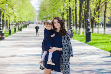 Mom and daughter on a walk in the summer park