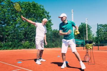 Tennis instructor with senior citizen on a tennis class