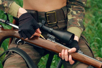 Hunter loading bullet to carbine with optical-sight