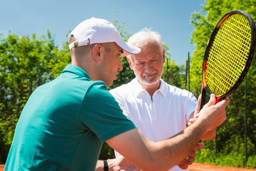 Senior man having tennis lesson