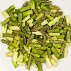 Close up on sliced pieces of green asparagus on a white plate