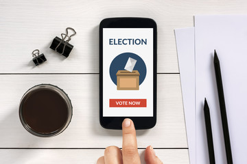 Online voting concept on smart phone screen with office objects on white wooden table. All screen content is designed by me. Flat lay