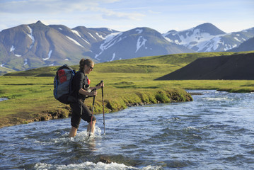 Female hiker crossing a river on the Laugavegur trail on Iceland.