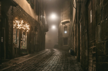 Foto op Plexiglas Smal steegje Old European narrow empty street of medieval town on a foggy evening. Taken in Bergamo, Citta Alta, Lombardia