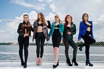 Group of sexy models girls in black bra and leather jackets on t