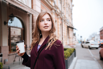 Pensive woman drinking coffe on the street of the city