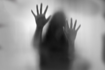 Horror woman behind the matte glass in black and white. Blurry hand and body figure abstraction