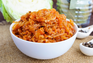 Braised cabbage with spices in a tomato sauce in a white bowl. Close-up.