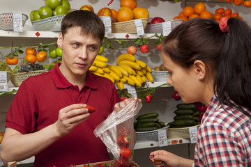 Assistant helping customer at vegetable counter of shop