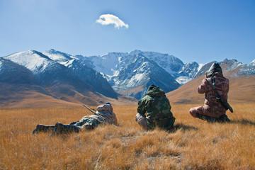 Three hunters looking through binoculars in mountains of Tien Sh