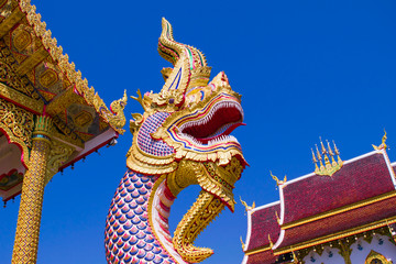 The religion art of naga or serpent head  statue with  blue sky background at Buddhist temple in  Thailand.