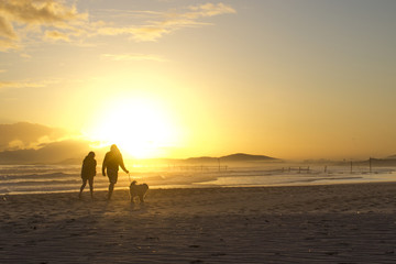 Beautiful beach sunset with silhouette of a lady and man walking their dog at Strand beach, Helderberg, Cape Town, Western Cape, South Africa.
