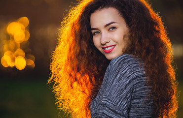 Smiling beautiful girl with curly, hair illuminated by the sun o