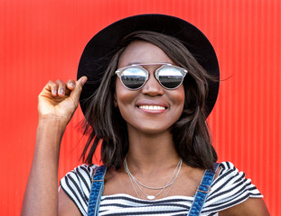 Beautiful smiling african woman in a black hat over colorful red