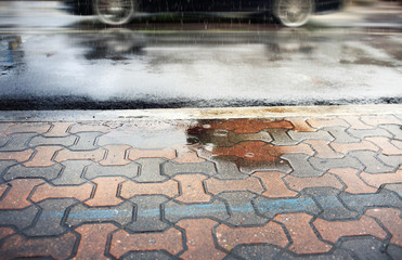 Walkway and wet street during rain fall,selective focus and motion blur.