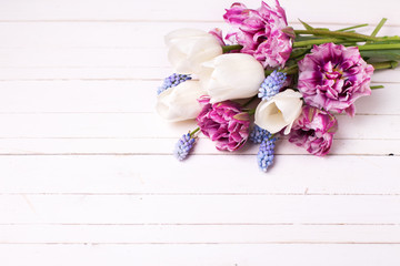 Fresh spring flowers on white wooden table.
