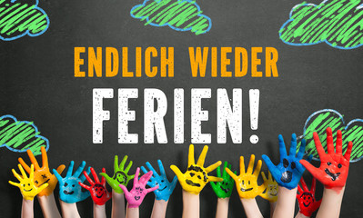 """angemalte Kinderhände vor Kreidetafel mit Nachricht """"Endlich wieder Ferien!"""""""