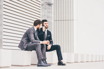 Two contemporary bearded businessman using technological devices