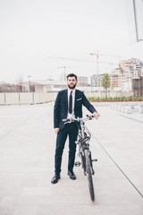 Young businessman with bicycle standing outdoors