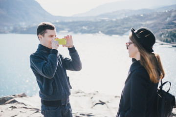 Man taking picture of his girlfriend using his smartphone near seaside and mountains. Travel together