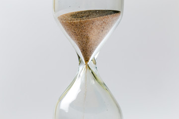 Sand flowing through an hourglass concept for time running out, background