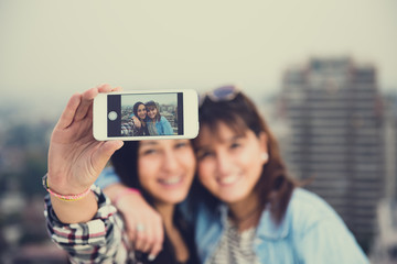 Two young women using their smart phone to take a self picture.