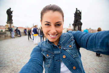 Young woman taking a selfie on charles bridge, Prague.