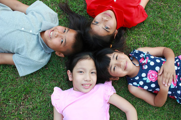 Four kids having fun in the park on green grass background.