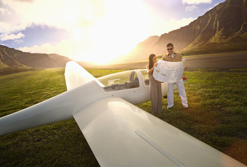 Couple reading map on glider airplane