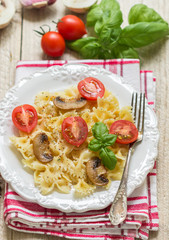 Warm salad of Farfalle with mushrooms and tomatoes