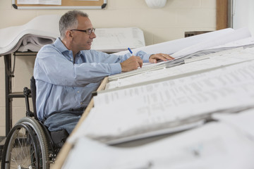 Caucasian architect in wheelchair working in office