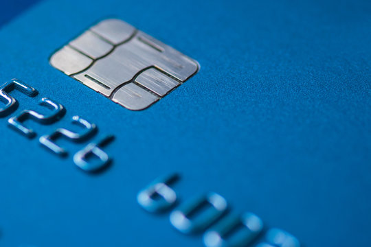 Credit Card blue with chip partial number selective focus close up macro empty space atm emv