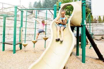 Mixed race sisters playing on playground