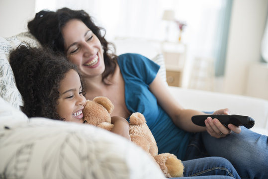 Mother and daughter watching television on sofa