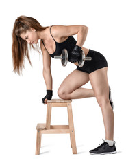 Cutout portrait of muscular young woman lifting a dumbbell for training her biceps leaning on the chair