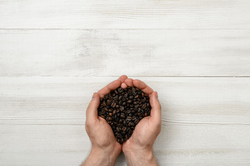 Close-up hands of man holding a handful coffee beans