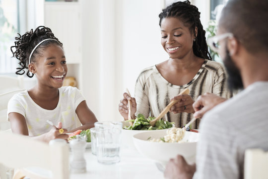 Black family eating salad at table