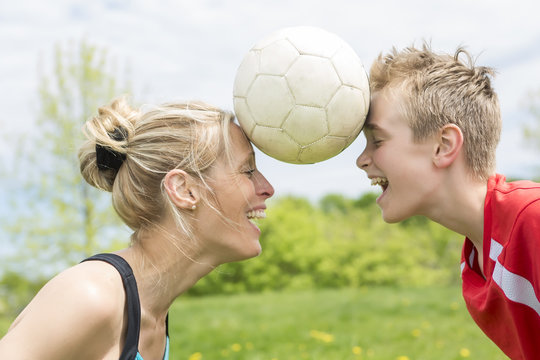 happy young family playing football outdoor on a summer day