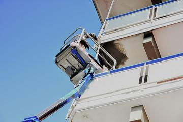 Un artigiano, ripara il balcone di una palazzina.