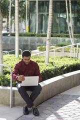 Black businessman using laptop outdoors