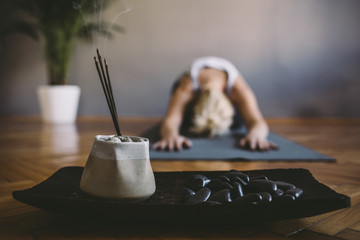Woman practicing yoga in the gym with incense sticks in foreground