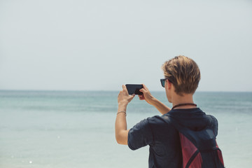 Man photographing seascape with smartphone